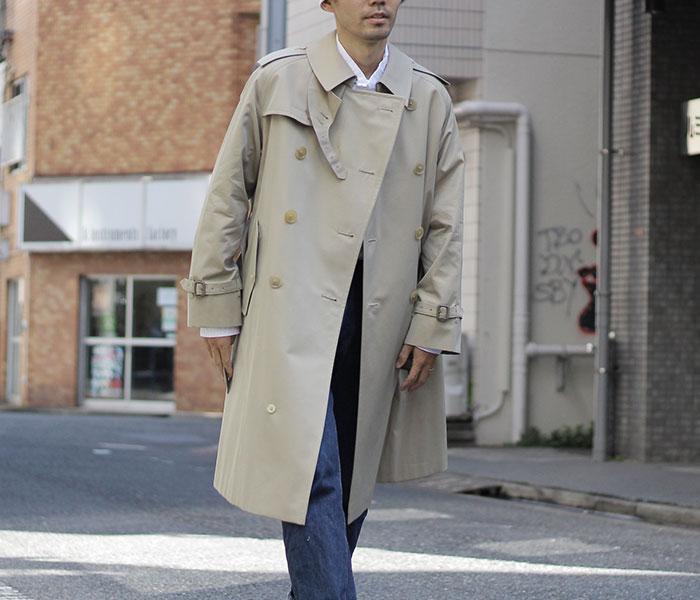 ベージュのトレンチコートを男性が着用