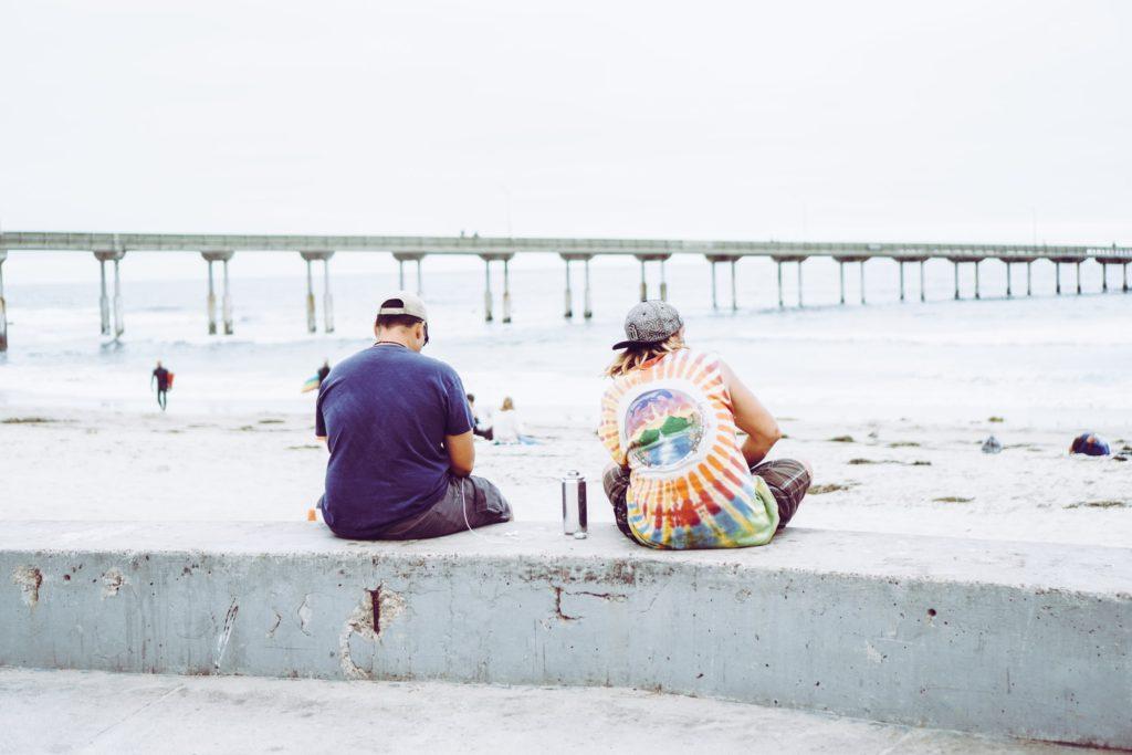 ヒッピーが海辺で座っている写真
